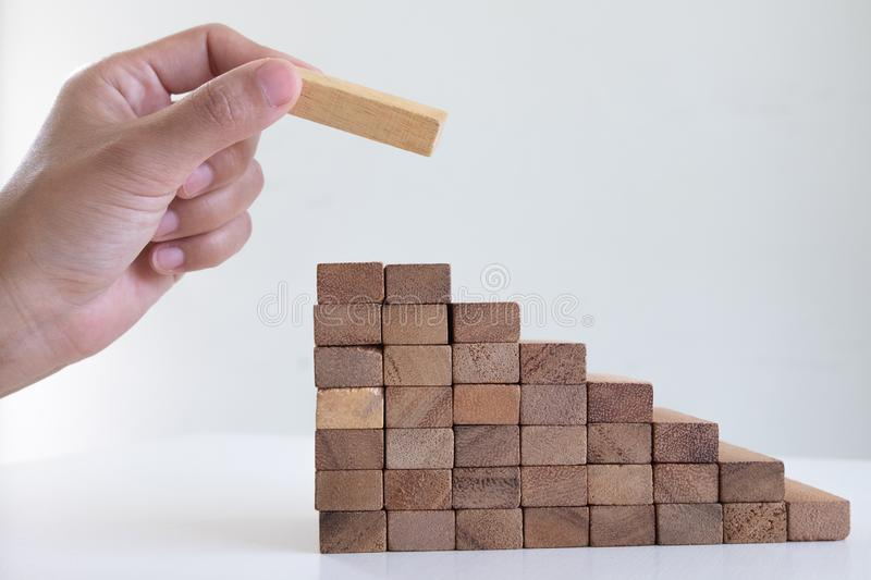 Image of hand holding blocks wood game to growing up of business. Risk of management and strategy plan stock photography