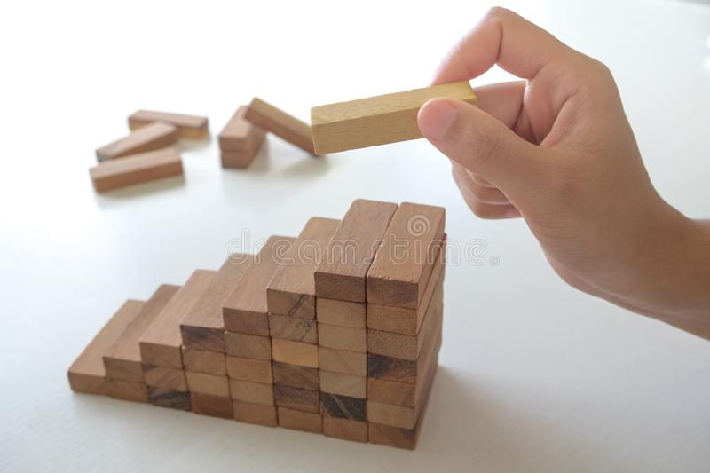 Image of hand holding blocks wood game to growing up of business. Risk of management and strategy plan stock images