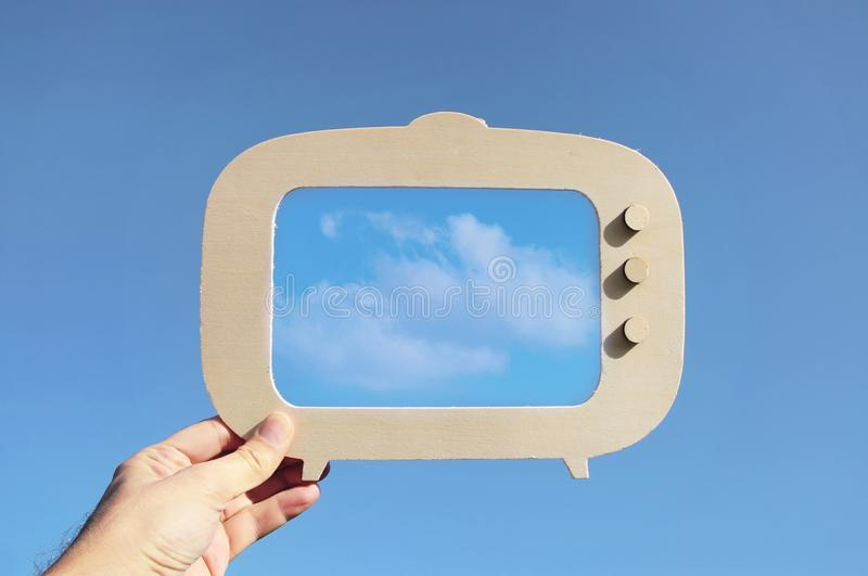 image of hand holding tv frame in front of sky with cloud. capture the moment or minimal concept. royalty free stock photography