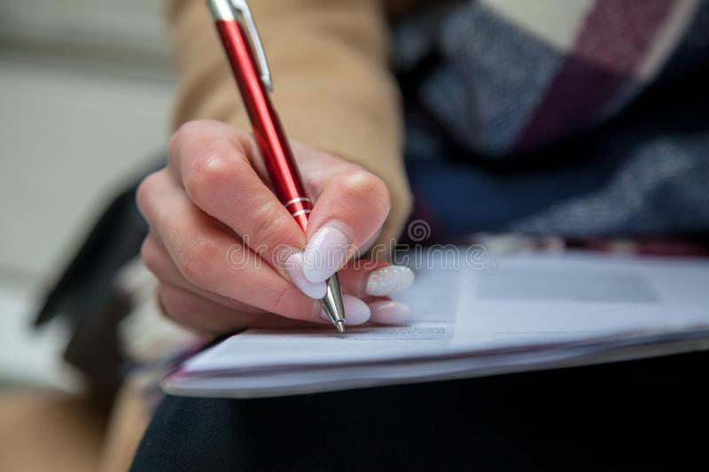 An image of a hand and pen completing a form. royalty free stock image