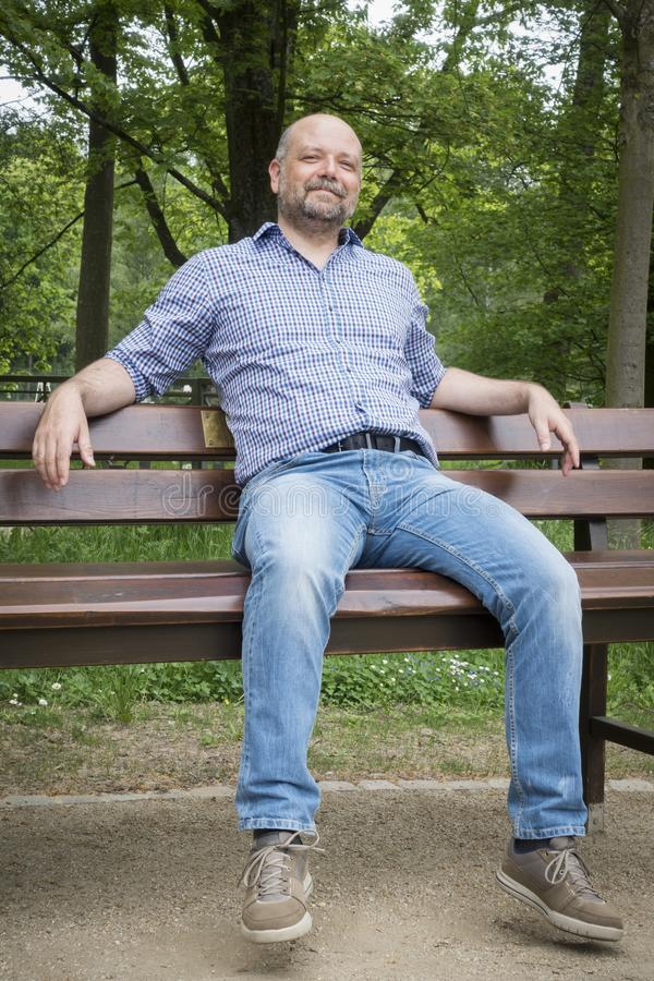 handsome bearded man sitting outdoors royalty free stock photography