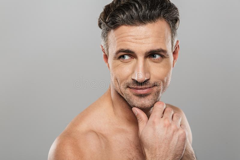 Handsome cheerful mature man. Looking aside. Image of handsome cheerful mature man standing isolated over grey wall background naked. Looking ae royalty free stock photo