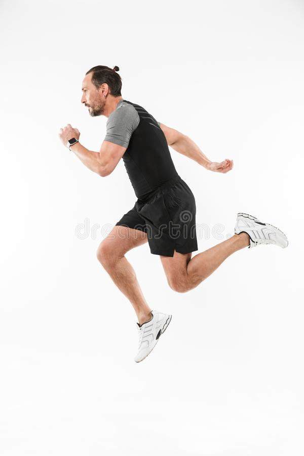 Handsome concentrated mature sportsman running stock photo