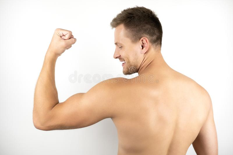 Image of handsome fit smiling man with naked torso showing biceps muscles white isolated background.  stock image