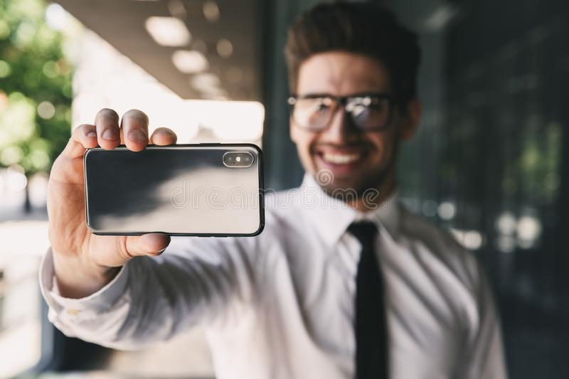 Business man near business center using mobile phone take a selfie. stock photo