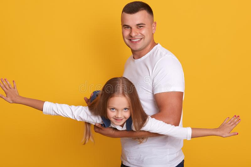 Image of handsome happy man teaching sweet lovely daughter to fly like plane, having fun together, spend time playing, isolated stock photos