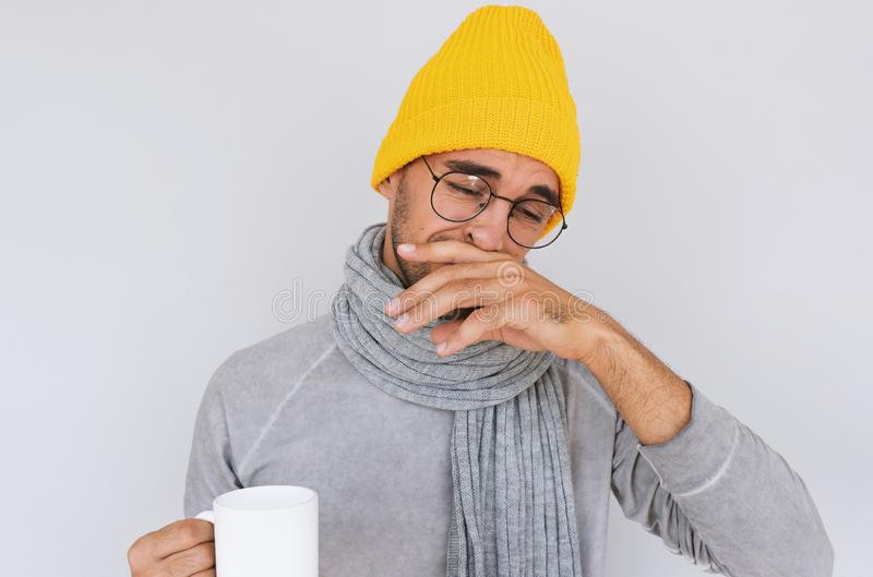 Image of handsome male caught cold when had walk outdoors in winter or autumn. Portrait of sick man have grippe wearing glasses, stock photos