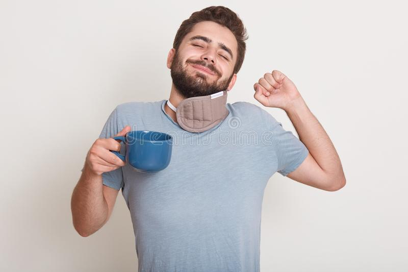 Image of handsome male has morning coffee, still sleeps, yawns, standing indoor isolated over white studio background, wearing stock photo