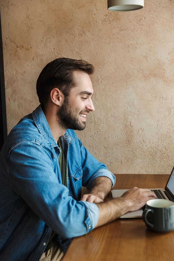 Image of handsome positive man smiling and using laptop while sitting at desk in cafe indoors royalty free stock photo