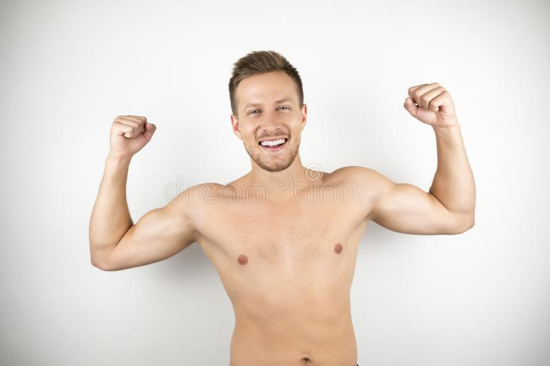 Image of handsome strong smiling man with naked torso showing muscles white isolated background royalty free stock photos