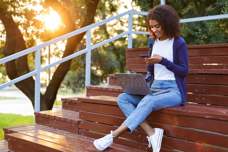 Young woman sitting outdoors in park on steps using laptop computer and mobile phone. stock photo