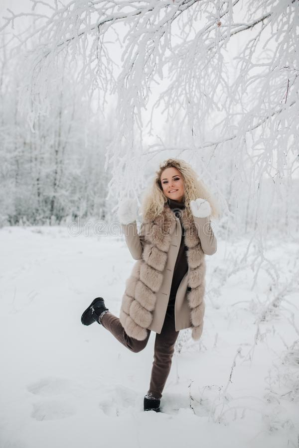Image of happy blonde woman on walk in winter forest stock photo
