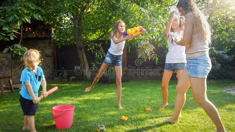 Photo of happy children having water gun fight at house backyard garden. Family playing and having fun outdoors at stock photography