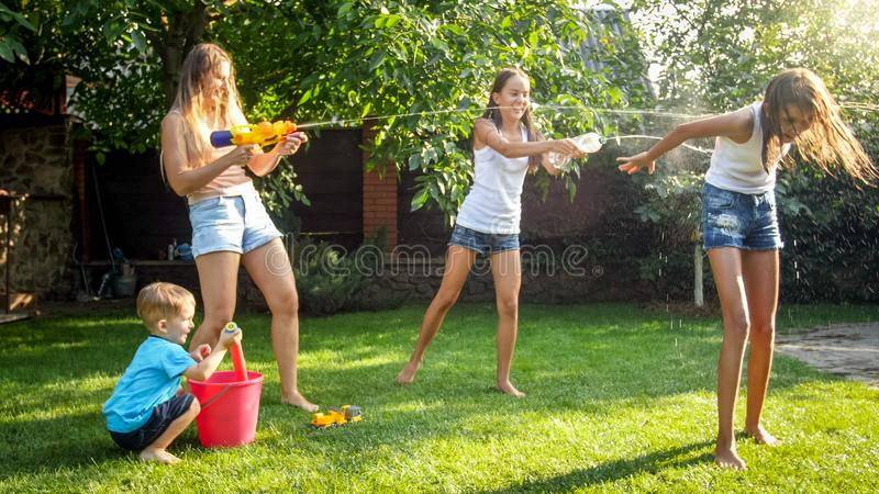 Image of happy children playing in the house backyard garden with water guns and garden hose. Family playing and having stock image