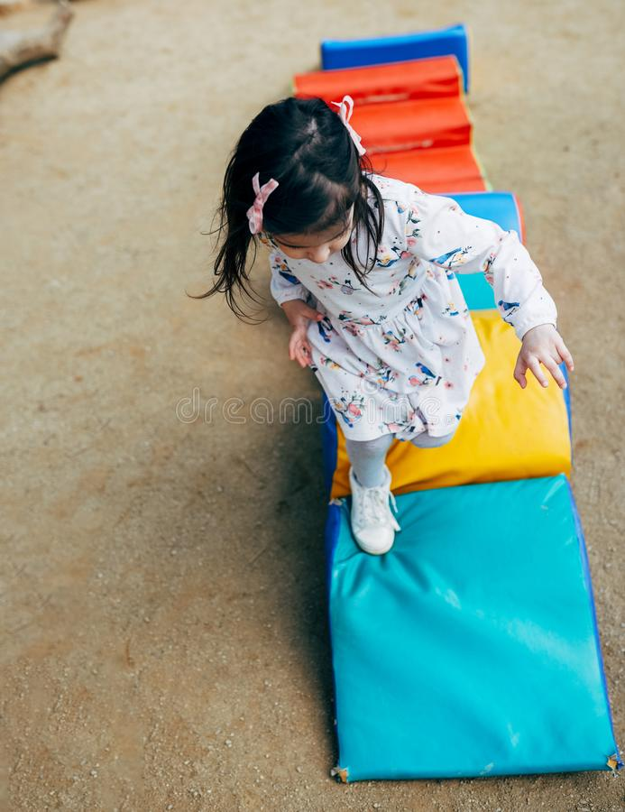 Image of happy cute little kid girl playing on colorful playground outdoor. Playful child running and jumping outside. stock images