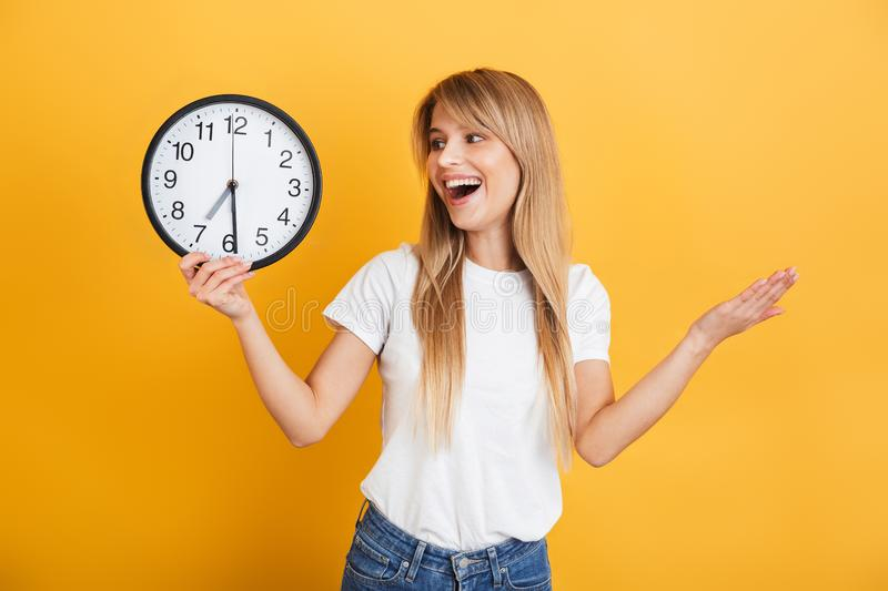 Cheerful young blonde woman posing isolated over yellow wall background dressed in white casual t-shirt holding clock royalty free stock photo