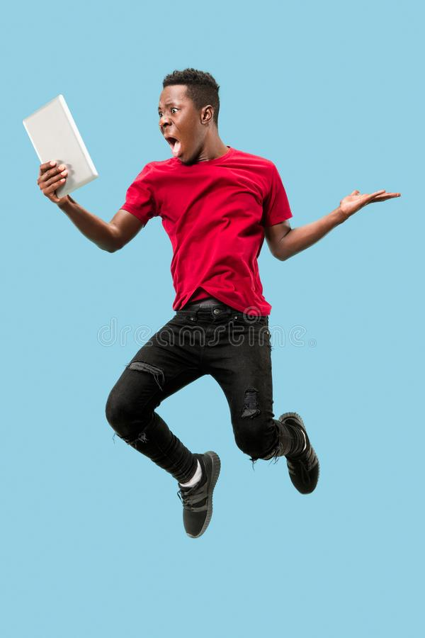 Image of happy excited young african man jumping isolated over yellow background using laptop royalty free stock images
