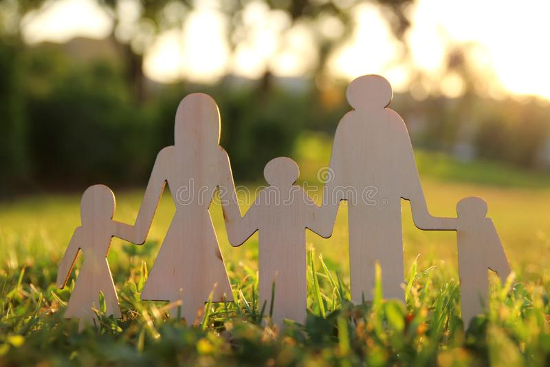 Image of happy family concept. wooden cut people holding hands together in green grass during sunset. Image of happy family concept. wooden cut people holding royalty free stock photos