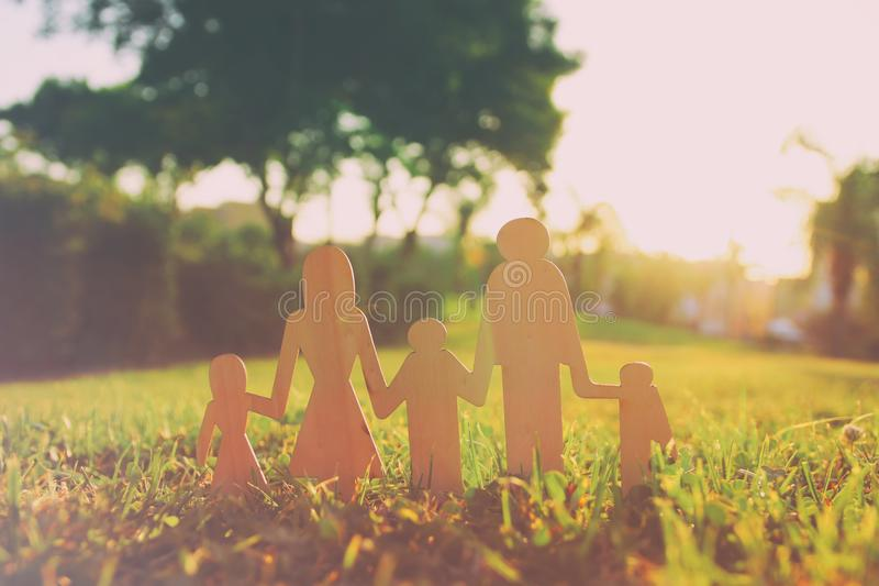 Image of happy family concept. wooden cut people holding hands together in green grass during sunset. Image of happy family concept. wooden cut people holding royalty free stock photo