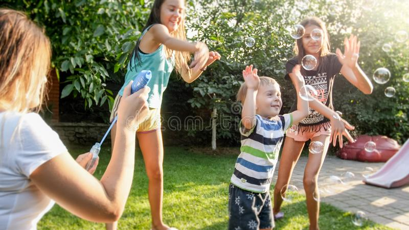 Photo of happy laughing children blowing and cathcing soap bubbles at house backyard. Family playing and having fun. Image of happy laughing children blowing and stock photography