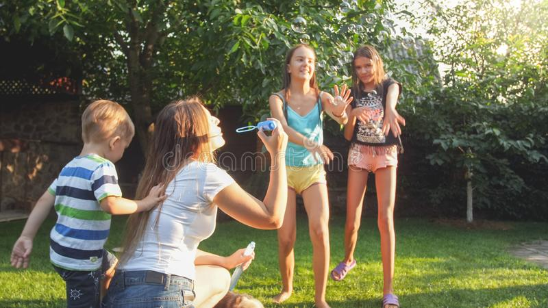 Photo of happy laughing children blowing and cathcing soap bubbles at house backyard. Family playing and having fun. Image of happy laughing children blowing and stock images