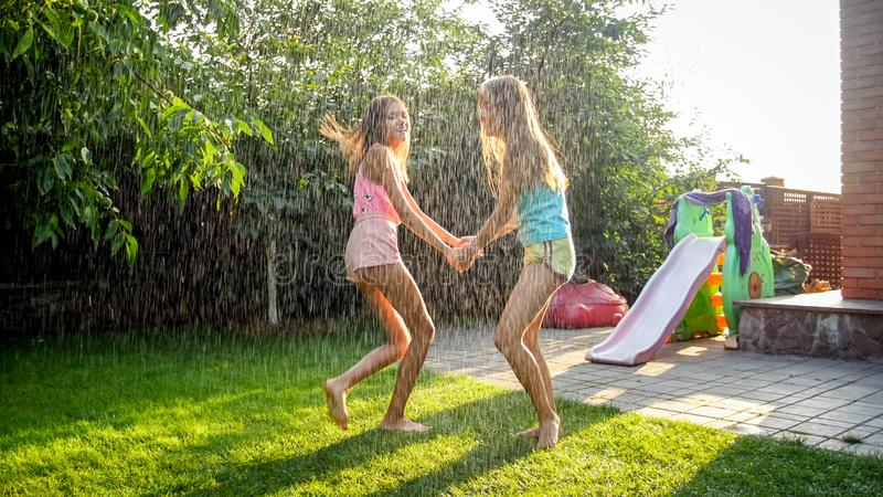 Photo of happy laughing children in wet clothes jumping and dancing under warm rain at garden. Family playing and having stock image