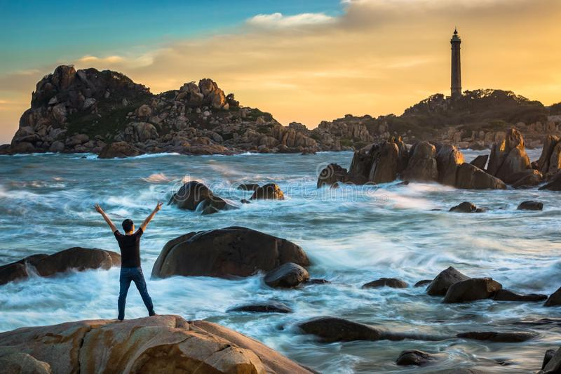 A Happy Man Celebrating Victory on The Top of A Big Rock by The Ocean stock photos