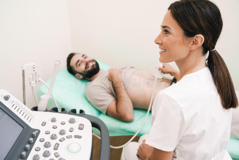 Image of happy man getting abdominal ultrasound scan by female doctor stock photos