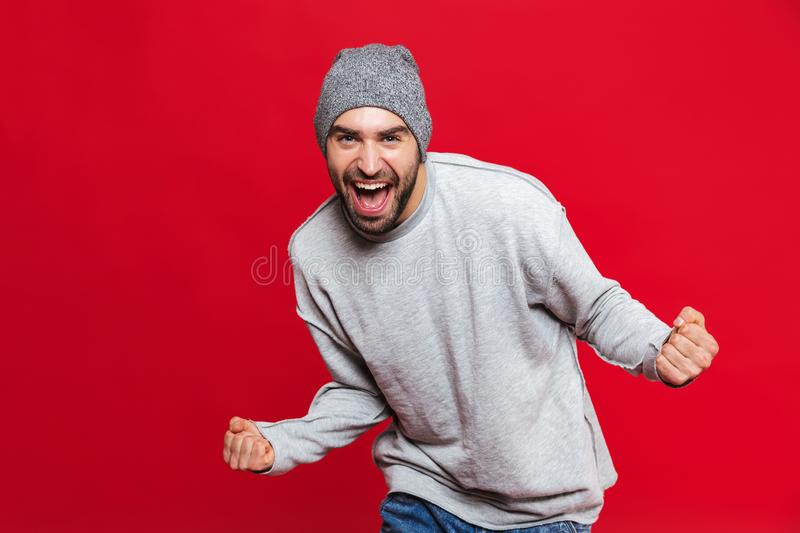 Image of happy man screaming and rejoicing isolated over red background stock photo