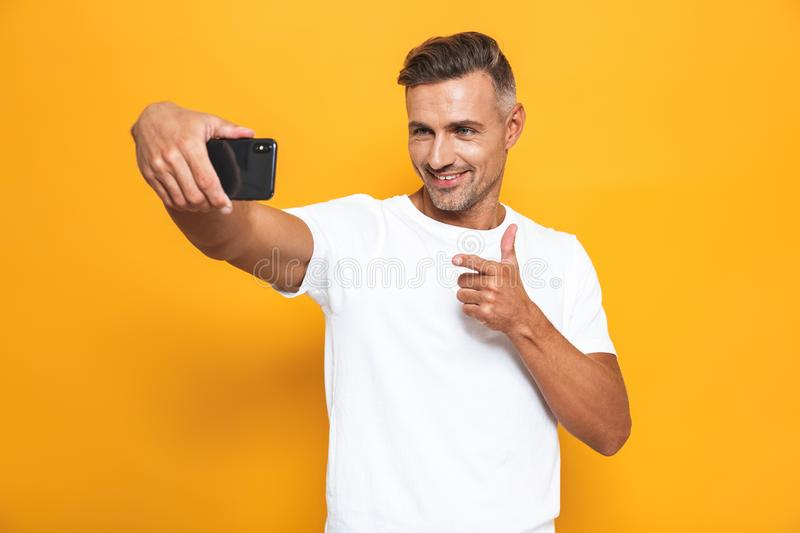 Image of happy man 30s in white t-shirt smiling and taking selfie photo on mobile phone isolated stock photo