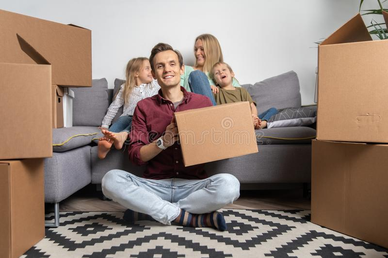 Image of happy man sitting on floor and women with boy and girl sitting on gray sofa among cardboard boxes. Image of happy men sitting on floor and women with royalty free stock photos
