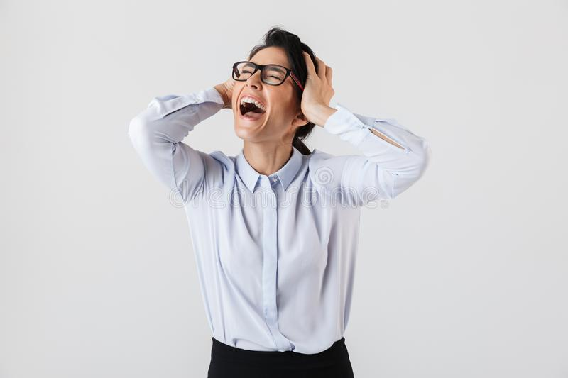 Image of happy secretary woman wearing eyeglasses screaming in the office, isolated over white background royalty free stock photos