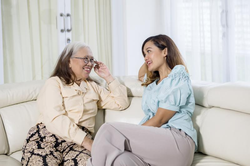 Happy senior woman chats with her daughter. Image of happy senior women sitting on the sofa while chatting with her daughter at home royalty free stock image