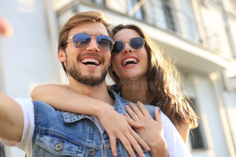 Image of a happy smiling cheerful young couple outdoors take a selfie by camera. stock image