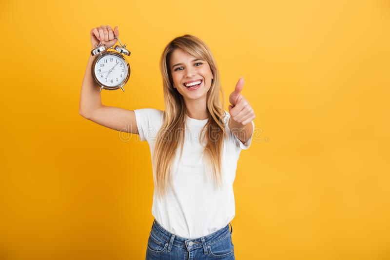 Happy smiling young blonde woman posing isolated over yellow wall background dressed in white casual t-shirt holding alarm clock. Image of a happy smiling young royalty free stock image