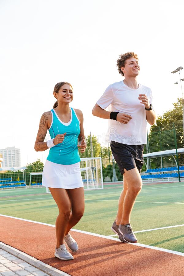 Image of happy woman and man running on stadium outdoors royalty free stock photos