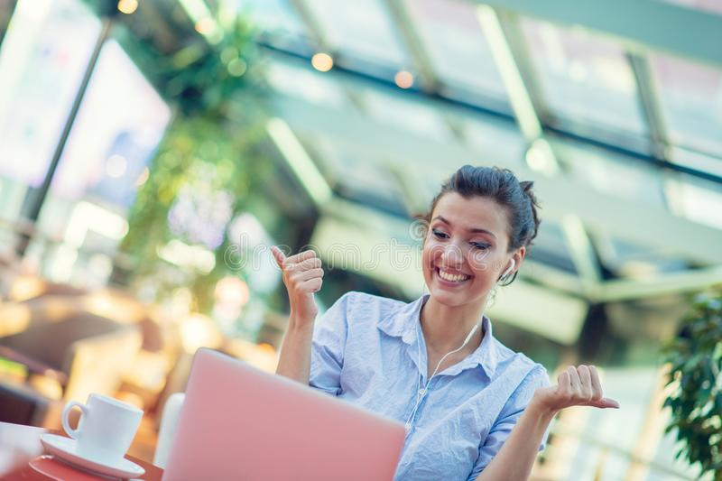 Image of happy woman using laptop while sitting at cafe. Young woman sitting in a coffee shop and working on laptop. Image of happy woman using laptop while stock images