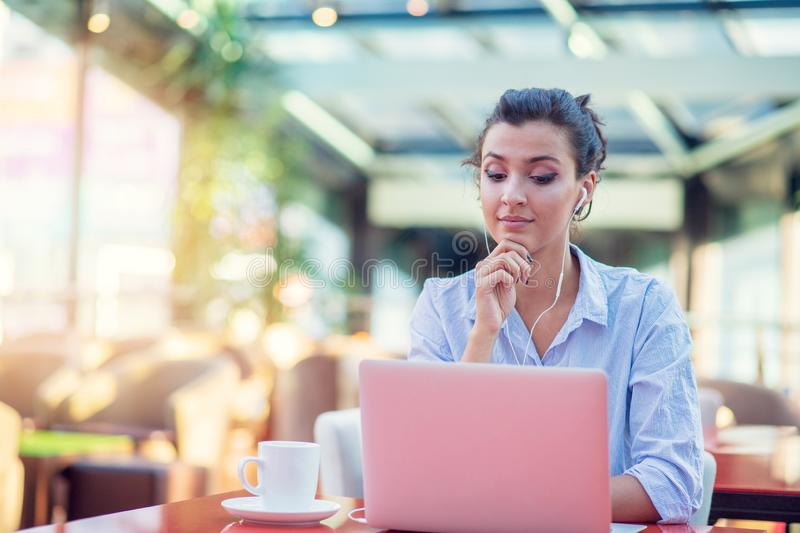 Image of happy woman using laptop while sitting at cafe. Young woman sitting in a coffee shop and working on laptop. Image of happy woman using laptop while stock photos