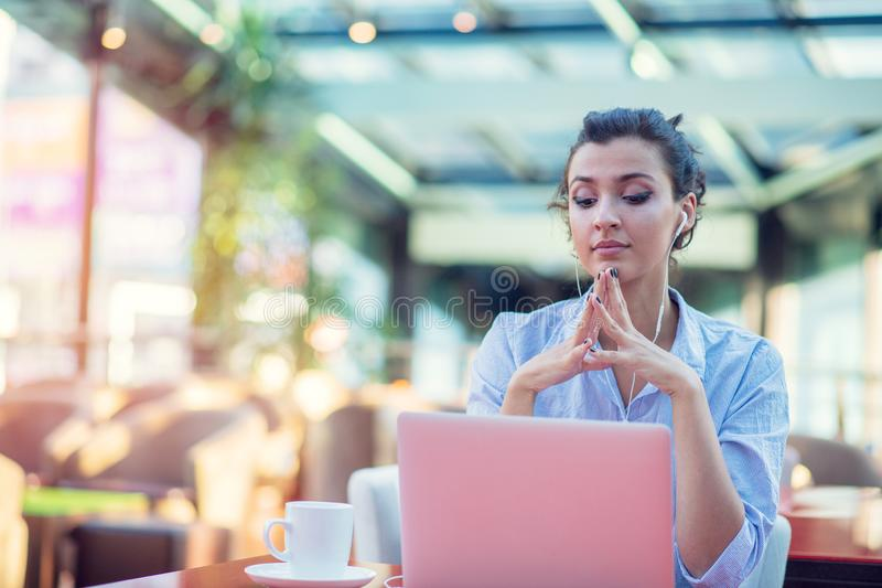 Image of happy woman using laptop while sitting at cafe. Young woman sitting in a coffee shop and working on laptop. Image of happy woman using laptop while royalty free stock image