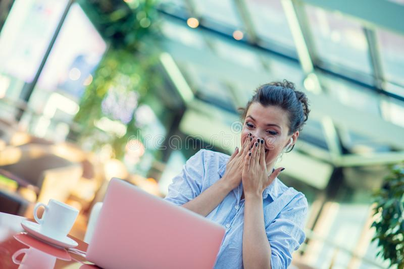 Image of happy woman using laptop while sitting at cafe. Young woman sitting in a coffee shop and working on laptop. Image of happy woman using laptop while royalty free stock photography