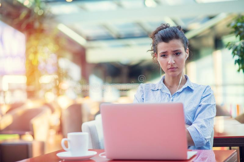 Image of happy woman using laptop while sitting at cafe. Young woman sitting in a coffee shop and working on laptop. Image of happy woman using laptop while royalty free stock images