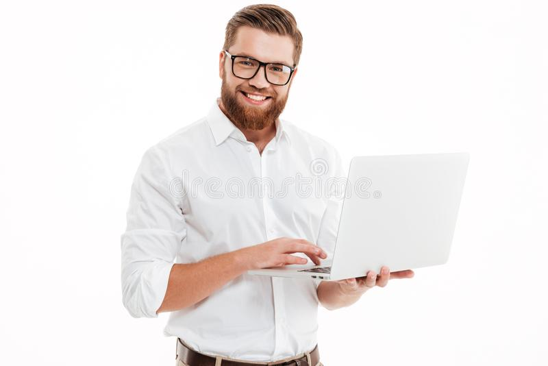 Happy young bearded man using laptop. royalty free stock photography