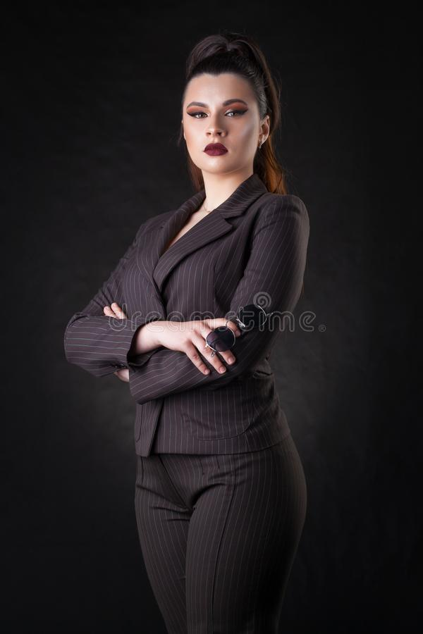 Happy young business woman posing over dark wall background. royalty free stock images
