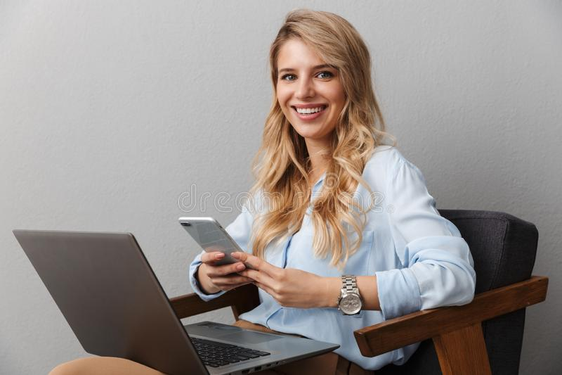 Happy young pretty blonde business woman posing  grey wall background using laptop computer and mobile phone. Image of a happy young pretty blonde business woman stock photo