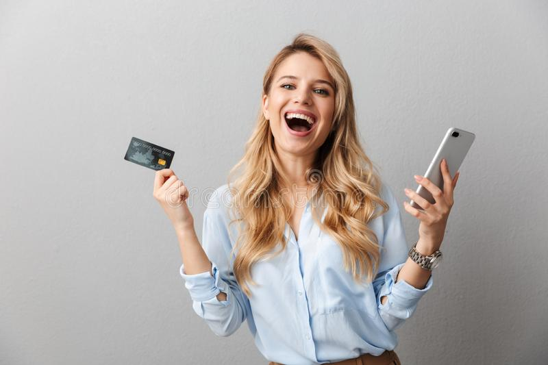 Happy young pretty blonde business woman posing isolated grey wall background holding credit card using mobile phone stock photography