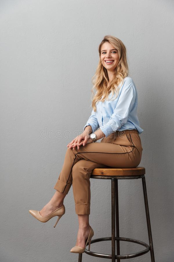 Blonde business woman posing isolated grey wall background sitting on stool royalty free stock photos