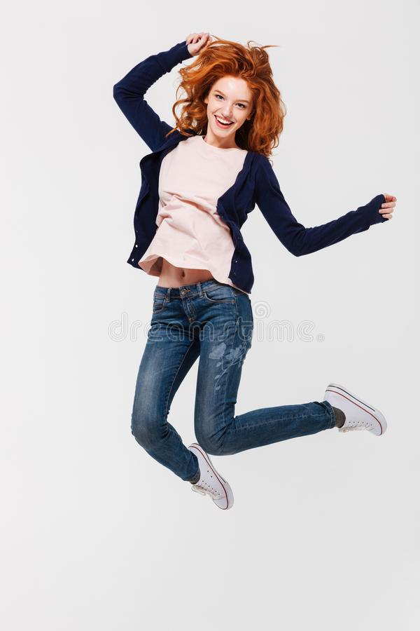 Happy young redhead lady jumping stock image