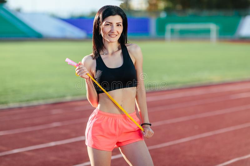 Portrait of happy young sports brunette woman in black top and rose shorts outdoors on stadium holding skipping rope royalty free stock images