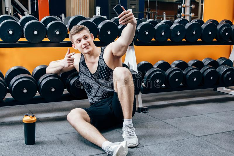 Image of happy young sportsman sitting in gym and make selfie. stock photos