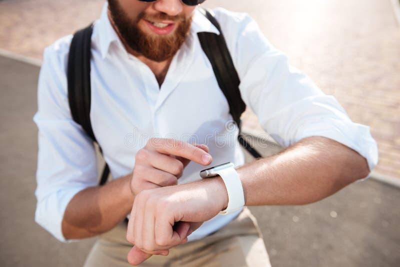 Image haute étroite cultivée de l'homme barbu de sourire à l'aide de la montre-bracelet images stock